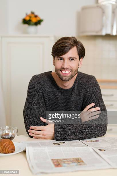 Portrait of smiling man sitting at breakfast table with newspaper