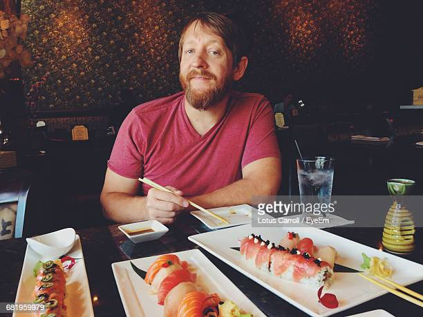 Portrait Of Smiling Man Sitting By Food On Table At Restaurant