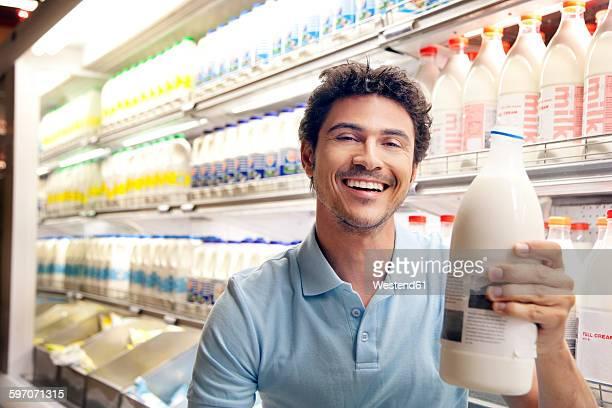 Portrait of smiling man sitting in front of fridge in a supermarket holding milk bottle