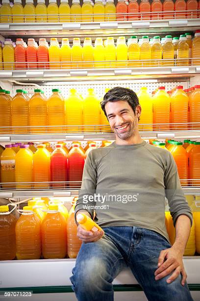 Portrait of smiling man sitting in front of fridge with rows of juice bottles in a supermarket