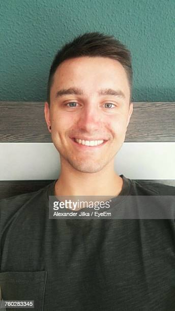 Portrait Of Smiling Man Sitting On Bench Against Wall