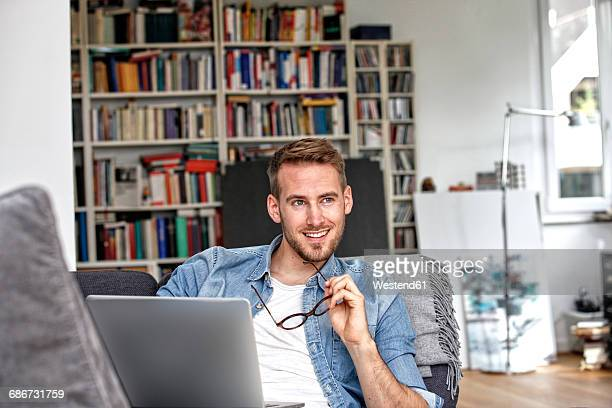 Portrait of smiling man sitting on couch with laptop in the living room