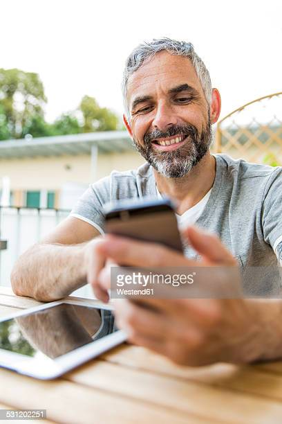 Portrait of smiling man sitting on his balcony with digital tablet using smartphone