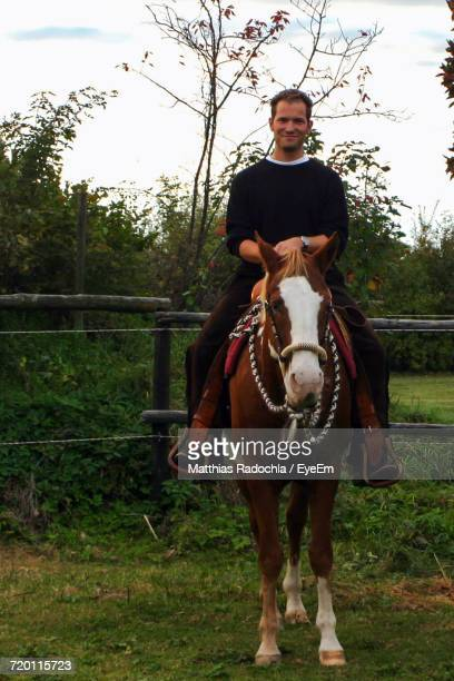 Portrait Of Smiling Man Sitting On Horse At Grassy Field