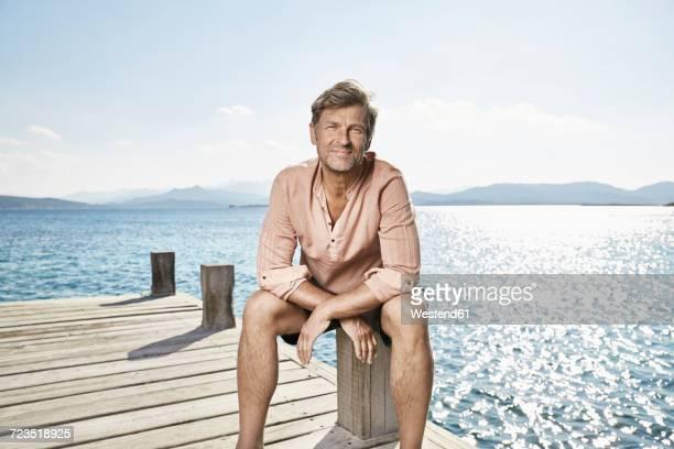 portrait of smiling man sitting on jetty - só um homem maduro imagens e fotografias de stock