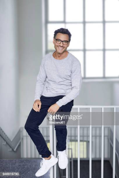 portrait of smiling man sitting on railing of staircase - gray shoe stock pictures, royalty-free photos & images