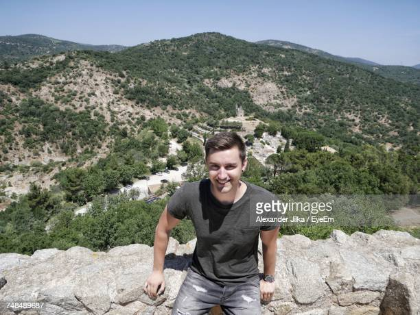 Portrait Of Smiling Man Sitting On Retaining Wall Against Mountains