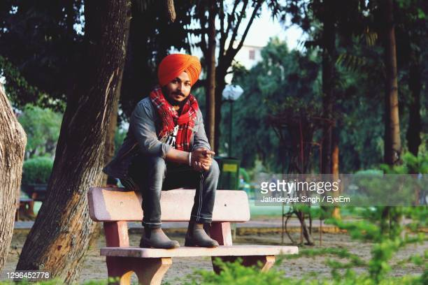 portrait of smiling man sitting on seat against trees - chandigarh stock pictures, royalty-free photos & images