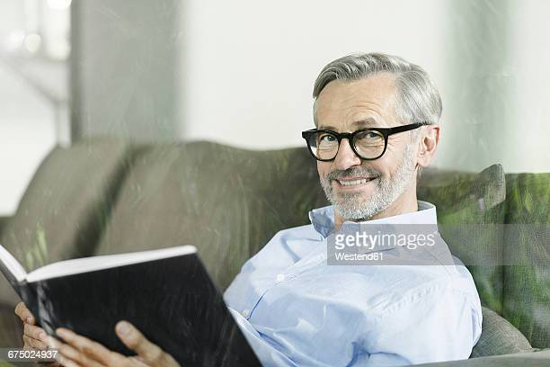 portrait of smiling man sitting on the couch with book - shirt stock pictures, royalty-free photos & images
