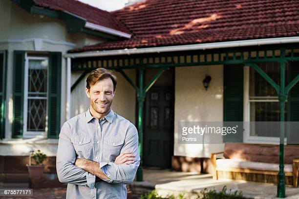 Portrait of smiling man standing against house