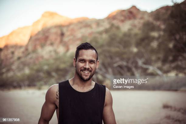 portrait of smiling man standing against mountain at desert - northern territory australia stock photos and pictures