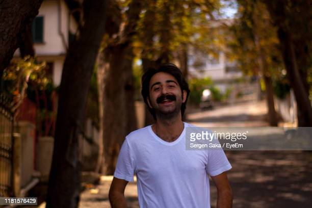 portrait of smiling man standing amidst trees on road - saka stock pictures, royalty-free photos & images