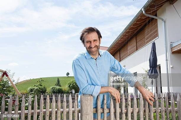 Portrait of smiling man standing in garden behind wooden fence