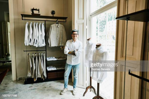 Portrait of smiling man standing in mens boutique while shopping for shirts