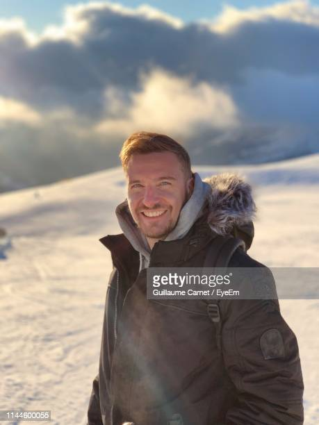 portrait of smiling man standing in snow - carnet stock photos and pictures
