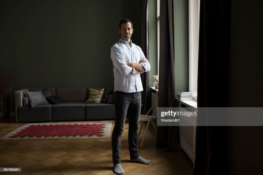 Portrait of smiling man standing near window in his living room : Stock-Foto