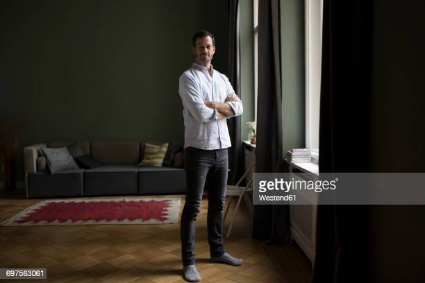 portrait of smiling man standing near window in his living room - orgoglio foto e immagini stock