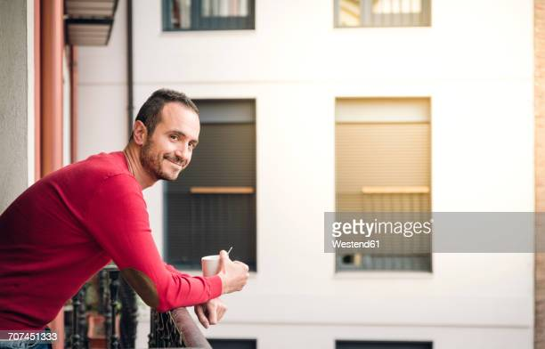 Portrait of smiling man standing on balcony with coffee mug