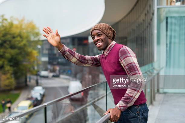 Portrait of smiling man standing on terrace waving while looking at distance
