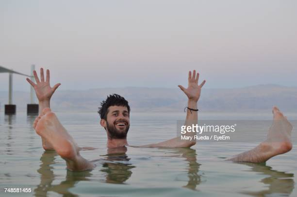 Portrait Of Smiling Man Swimming In Lake By Mountain