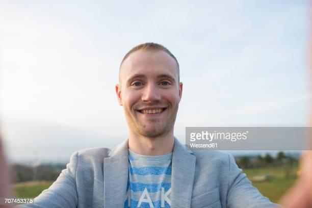 portrait of smiling man taking selfie - selbstportrait stock-fotos und bilder