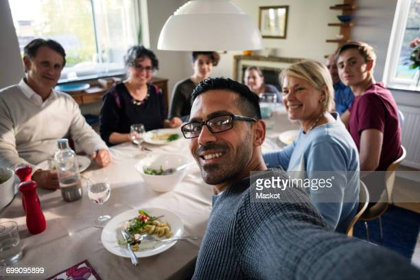 portrait of smiling man taking selfie with family and friends at dinner party - fugitive stock photos and pictures