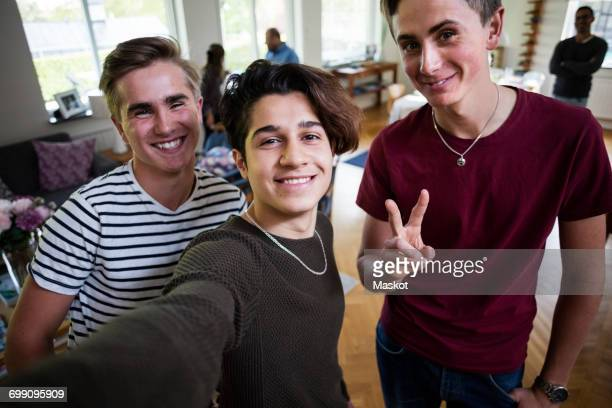 portrait of smiling man taking selfie with friend at home - fugitive stock photos and pictures
