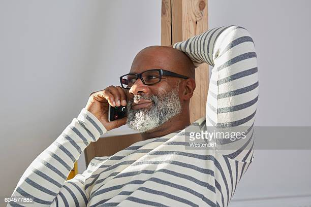 Portrait of smiling man telephoning with smartphone at home