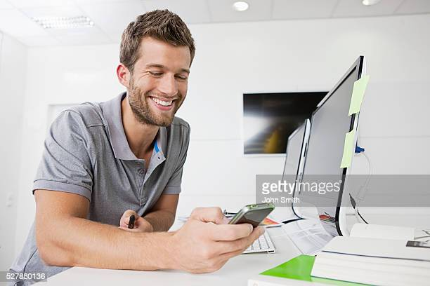Portrait of smiling man text messaging in office
