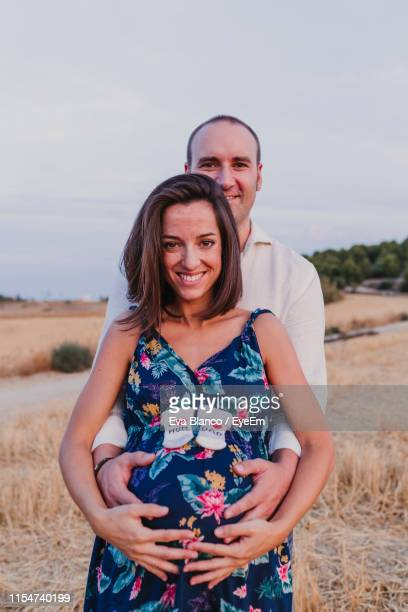 portrait of smiling man touching pregnant girlfriend belly while standing on field - casal heterossexual imagens e fotografias de stock