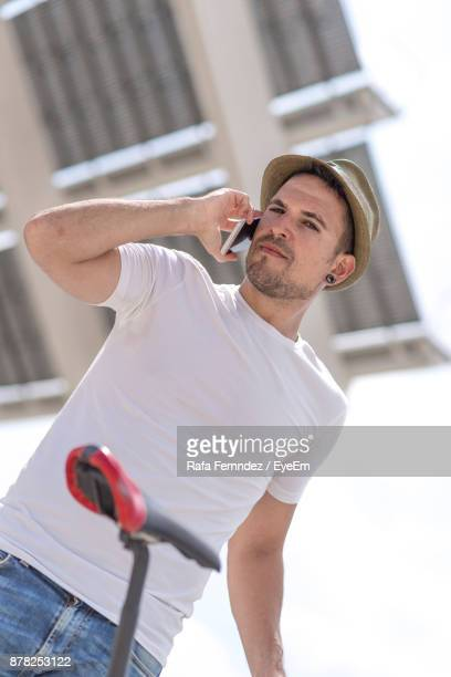 Portrait Of Smiling Man Using Mobile Phone While Standing Against Building
