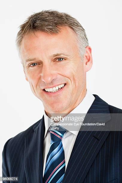 """portrait of smiling man wearing a suit - """"compassionate eye"""" fotografías e imágenes de stock"""