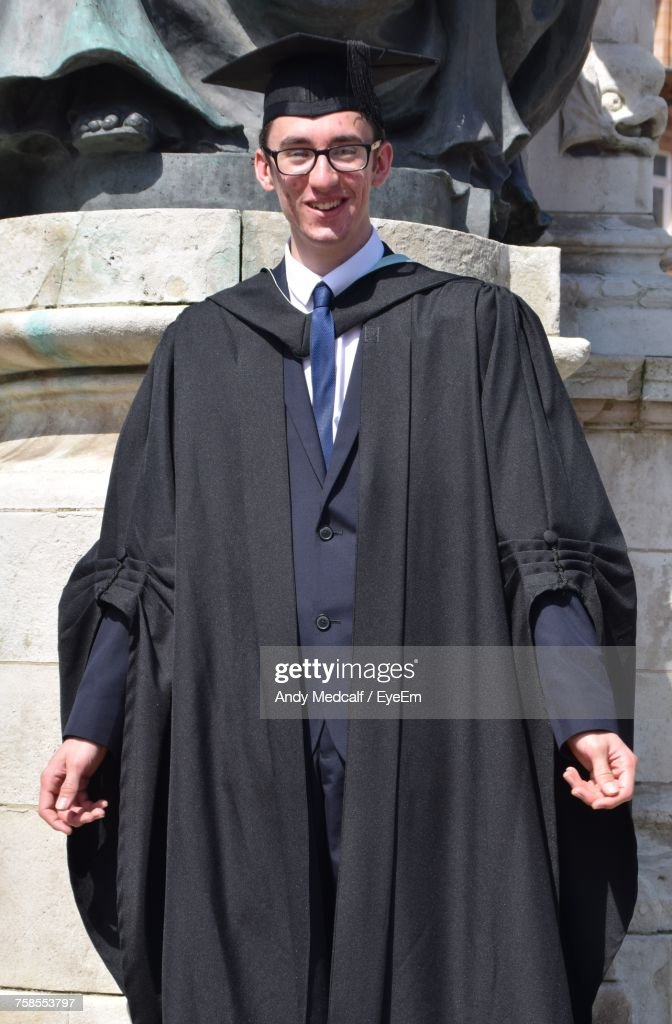 Portrait Of Smiling Man Wearing Black Graduation Gown On Sunny Day ...