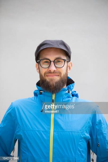 portrait of smiling man wearing blue rain jacket - blue jacket stock pictures, royalty-free photos & images