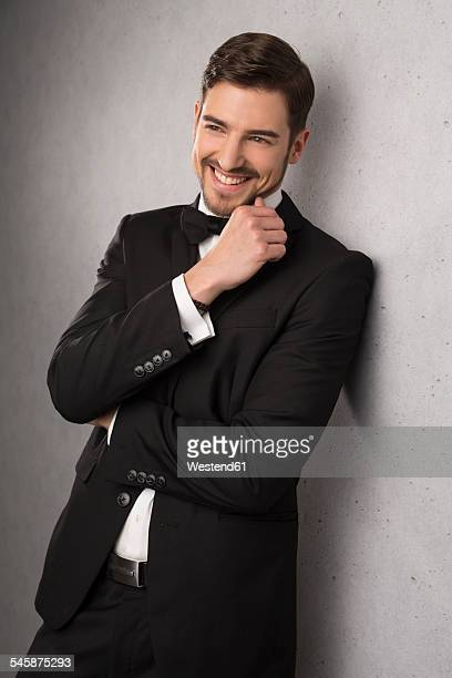 Portrait of smiling man wearing dinner jacket and bow leaning at wall
