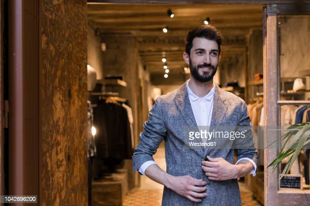 portrait of smiling man wearing jacket leaving menswear shop - jacket stock pictures, royalty-free photos & images