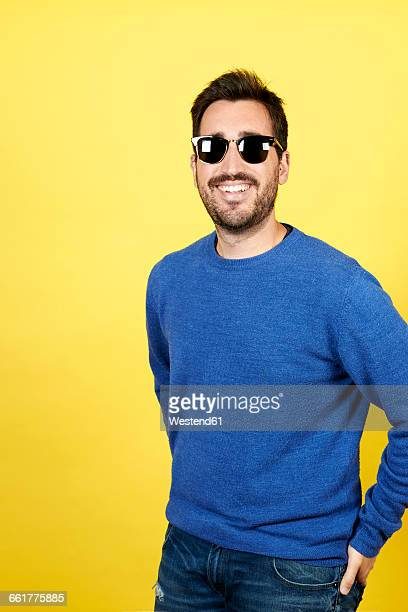 Portrait of smiling man wearing sunglasses in front of yellow background