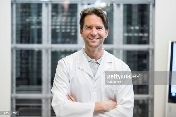 portrait of smiling man wearing work coat in factory - wissenschaft stock-fotos und bilder