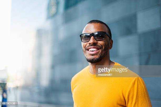 portrait of smiling man wearing yellow pullover and sunglasses - サングラス 男性 ストックフォトと画像