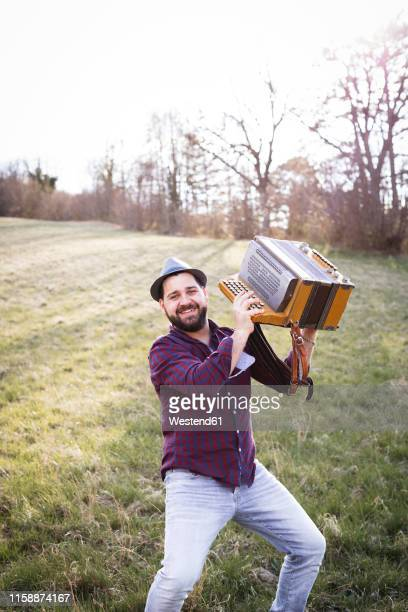 portrait of smiling man with accordion on a meadow - accordionist stock pictures, royalty-free photos & images