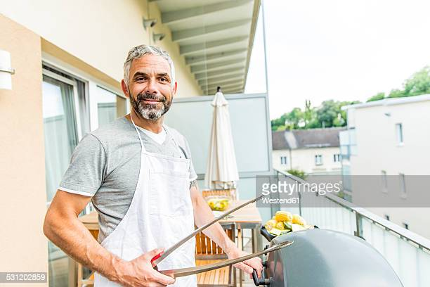 Portrait of smiling man with apron and tongs on his balcony