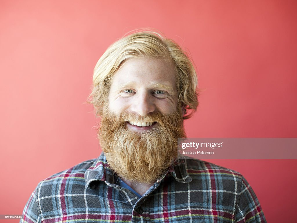 Portrait of smiling man with beard, studio shot : Stock Photo