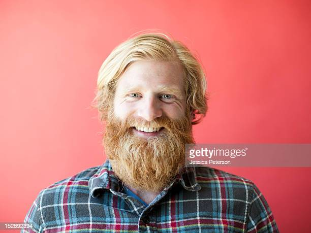 portrait of smiling man with beard, studio shot - vollbart stock-fotos und bilder