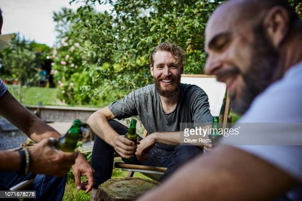 portrait of smiling man with beer bottle sitting together with friends in garden - men friends beer outside stock pictures, royalty-free photos & images