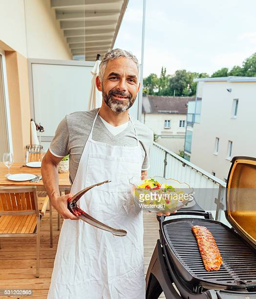 Portrait of smiling man with bowl of salad and tongs on his balcony