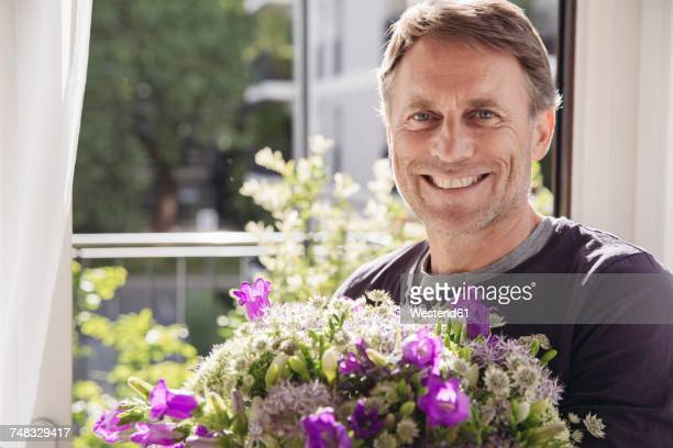 Portrait of smiling man with bunch of flowers