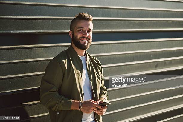 portrait of smiling man with cell phone standing in front of facade - pompadour stock pictures, royalty-free photos & images