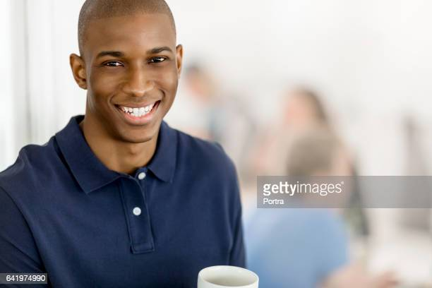 Portrait of smiling man with coffee cup in cafe