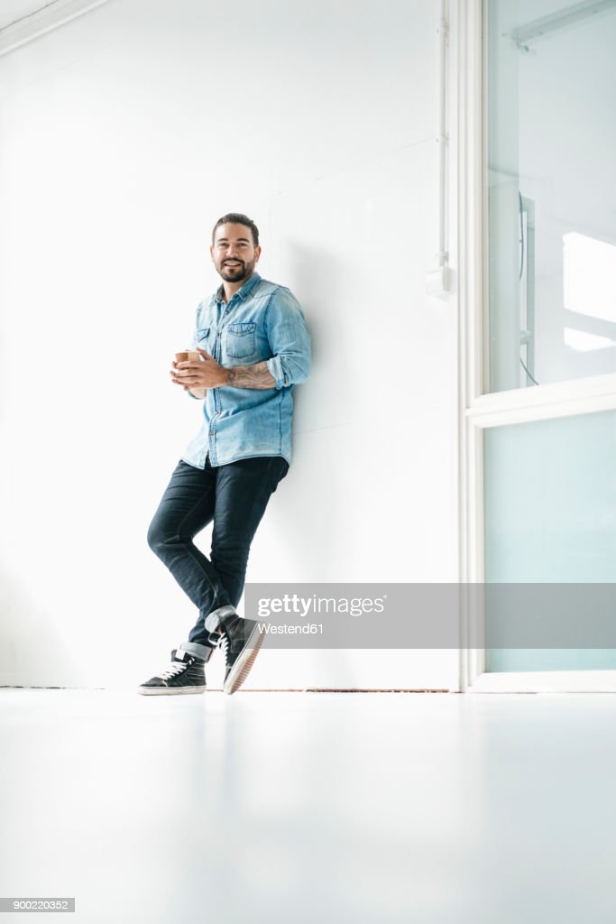 Portrait of smiling man with coffee to go leaning against wall in a loft : Stock Photo