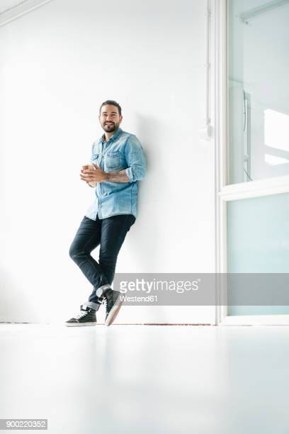 portrait of smiling man with coffee to go leaning against wall in a loft - lehnend stock-fotos und bilder